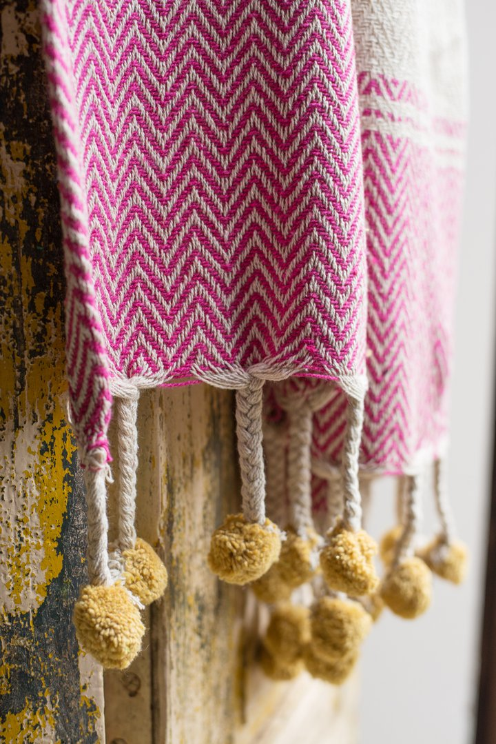 Pink cotton throw with tassels & yellow pom poms by Ian Snow