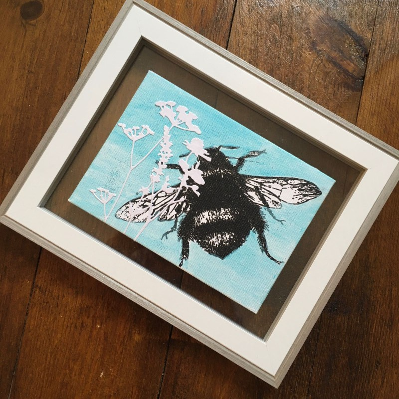 Screen printed bee on canvas in white / grey clear backed frame