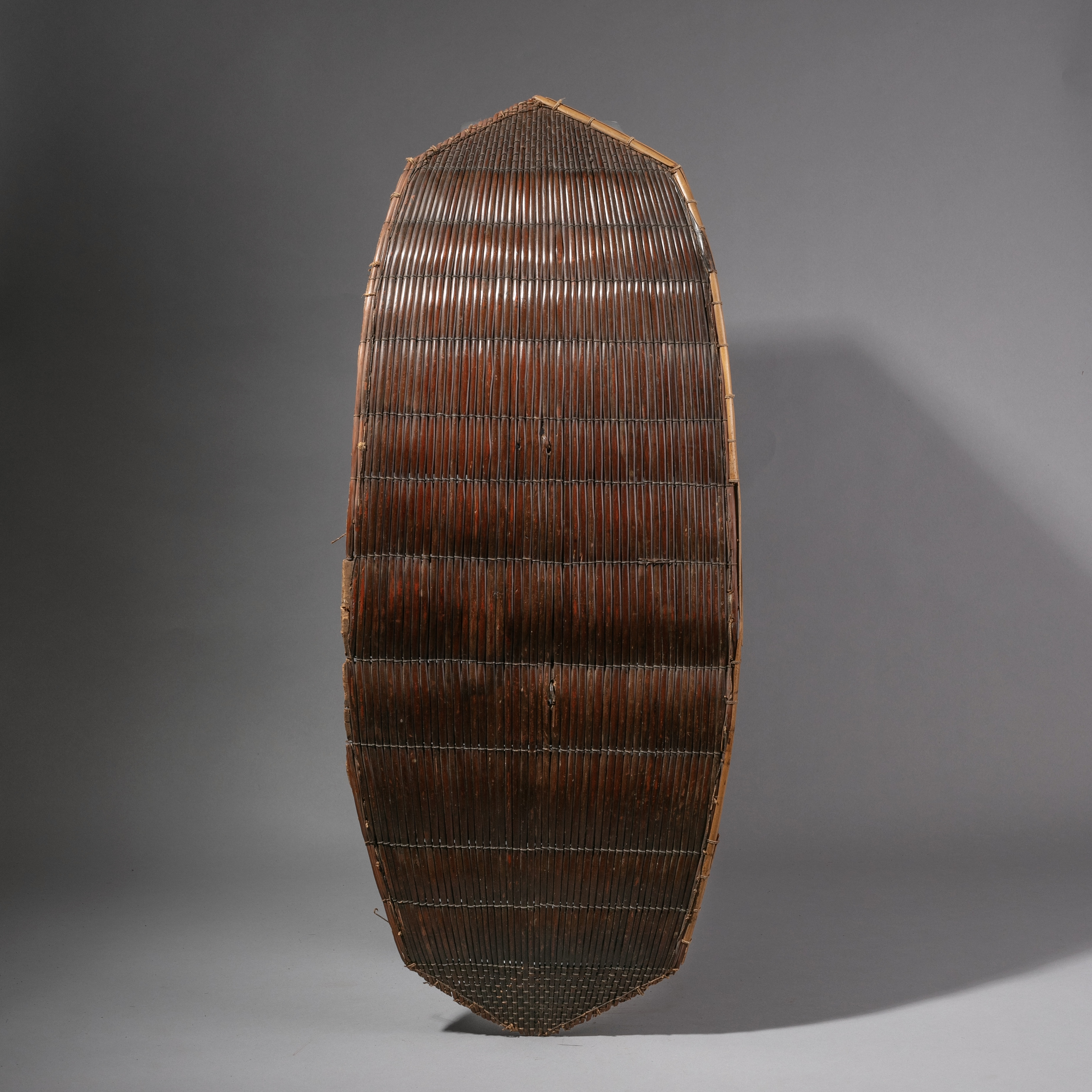 A SIMPLE RED FIBRE SHIELD WITH MASK HANDLE FROM THE CONGO ( No 1222)