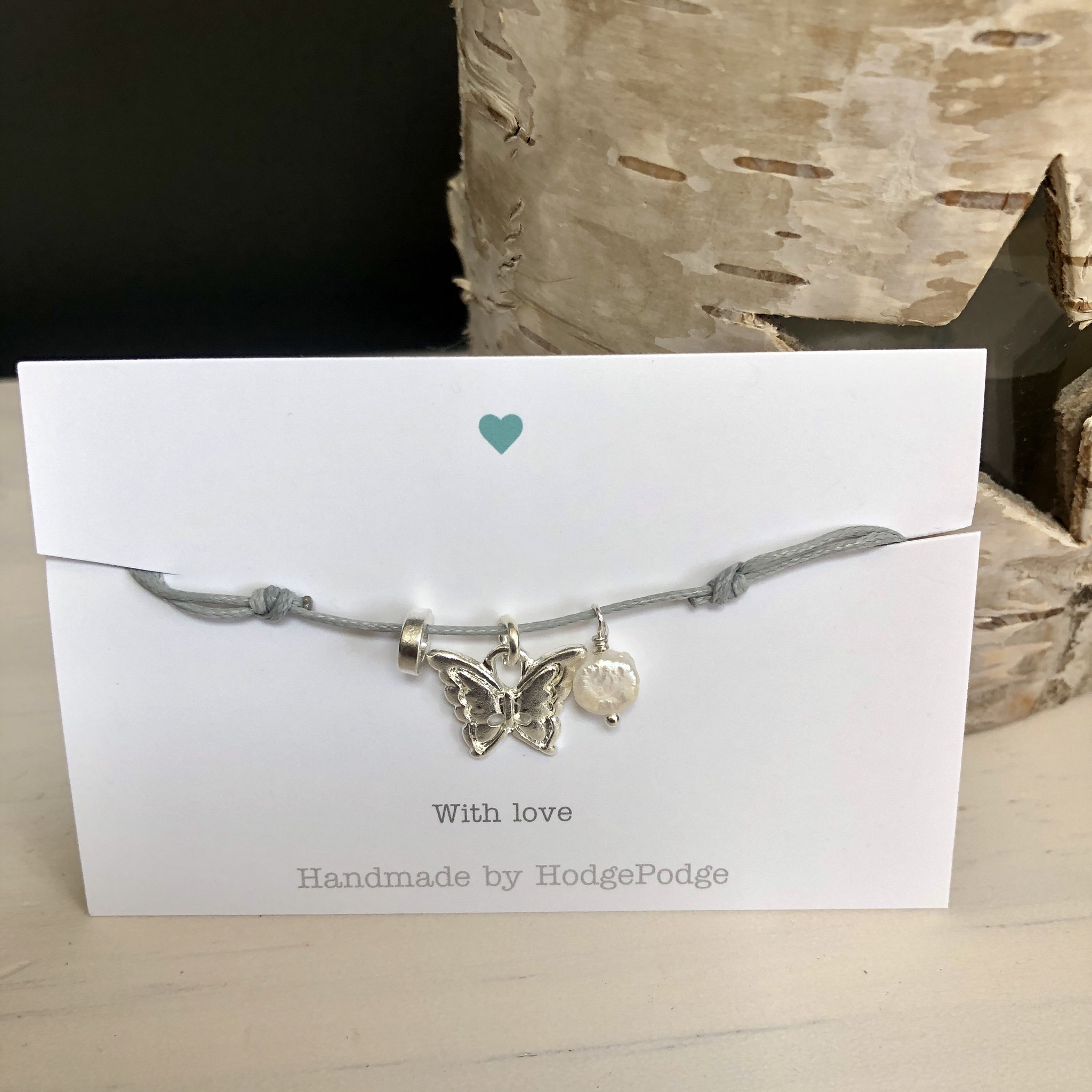 Adjustable cord bracelet in grey with butterfly charm and pearl.