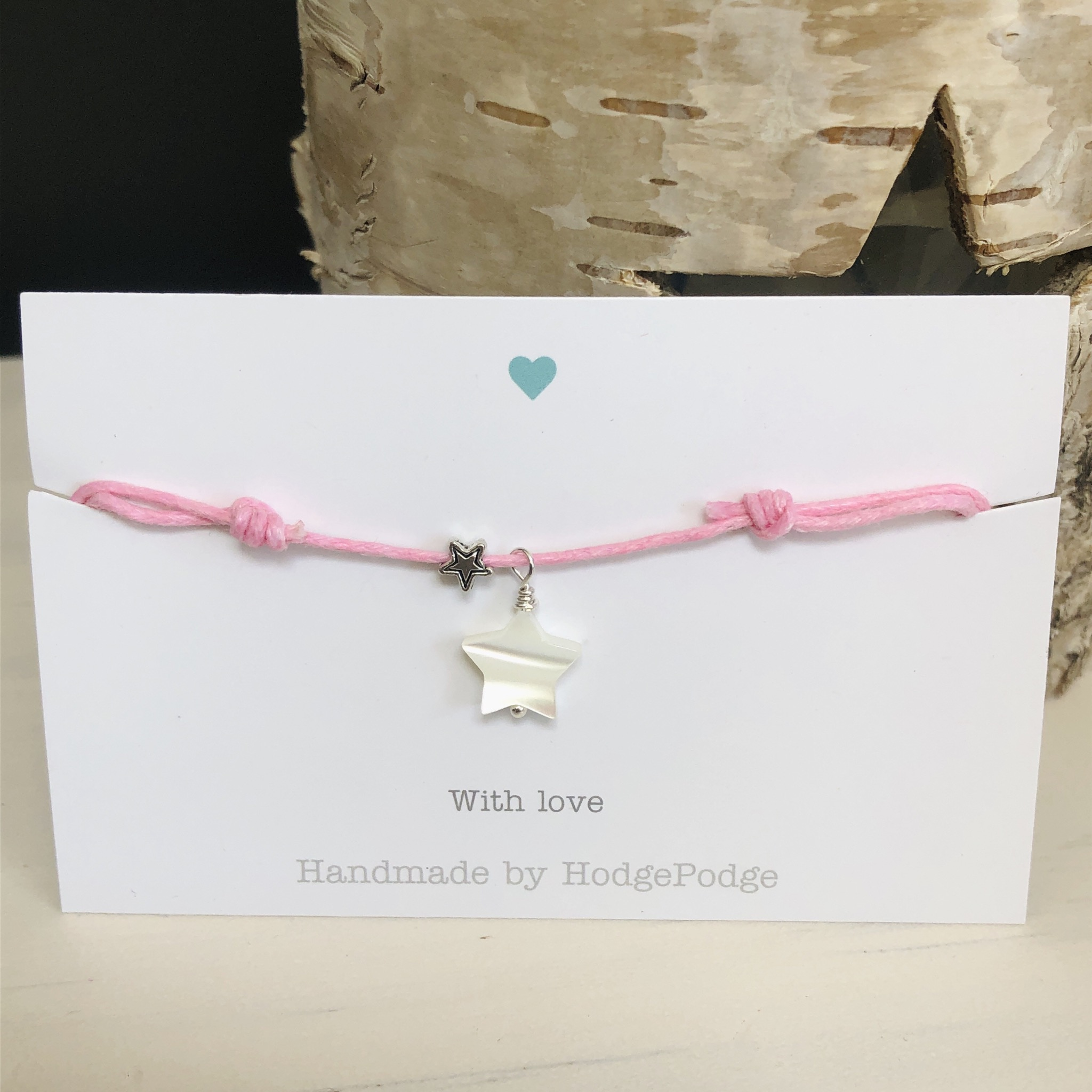 Adjustable cord bracelet with shell star charm and star bead.