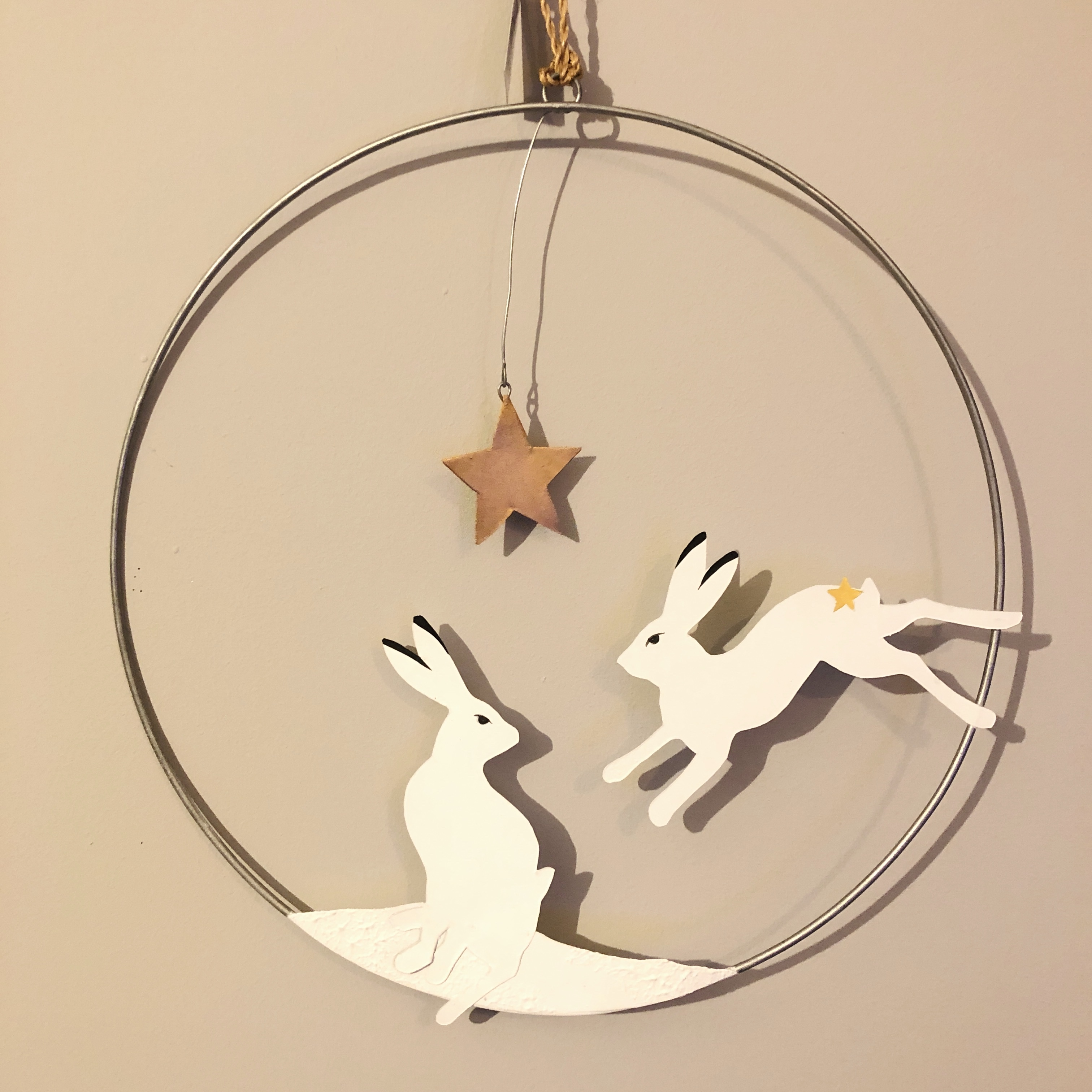 Artic hare hanging Christmas wreath by shoeless joe