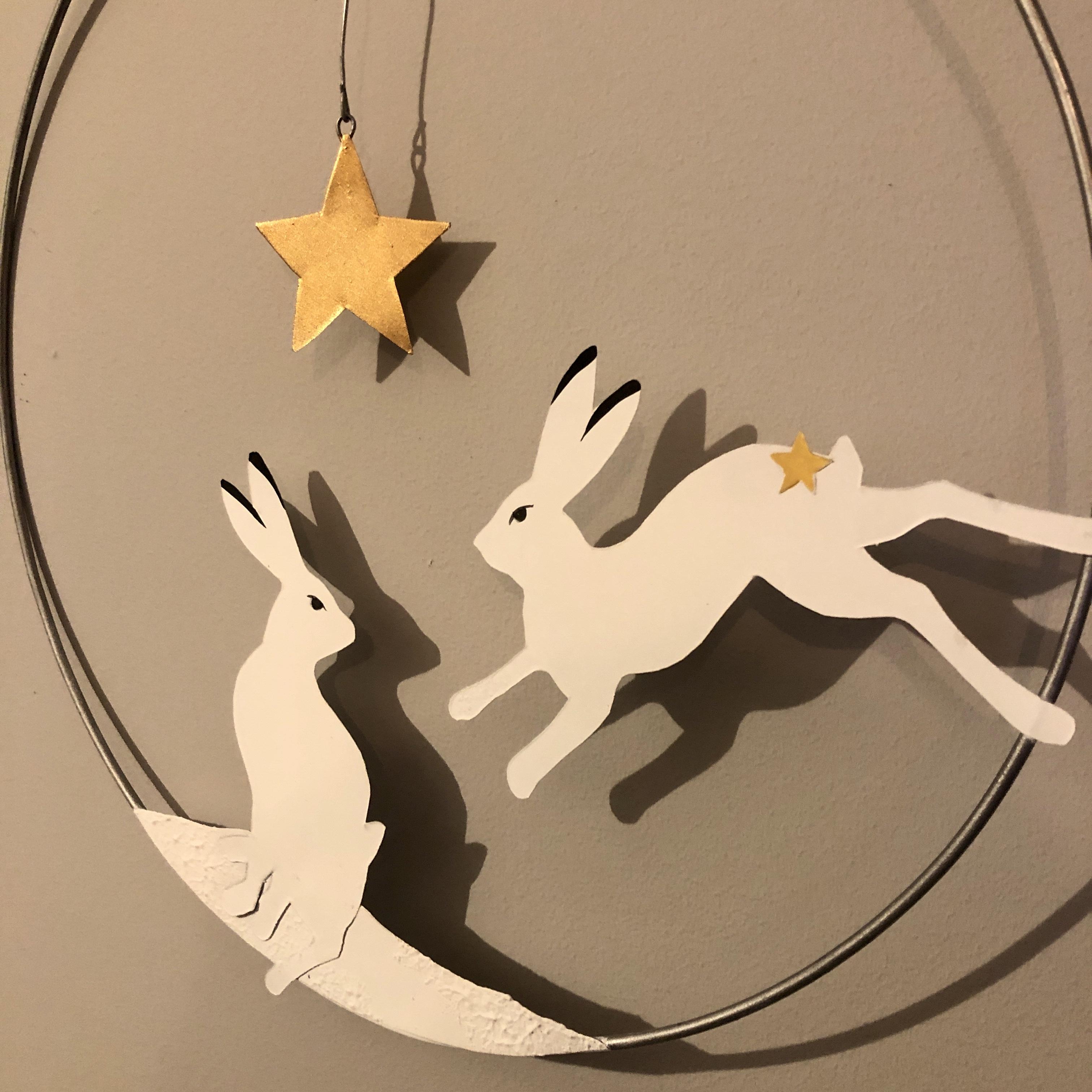Artic hare hanging Christmas wreath by shoeless joe