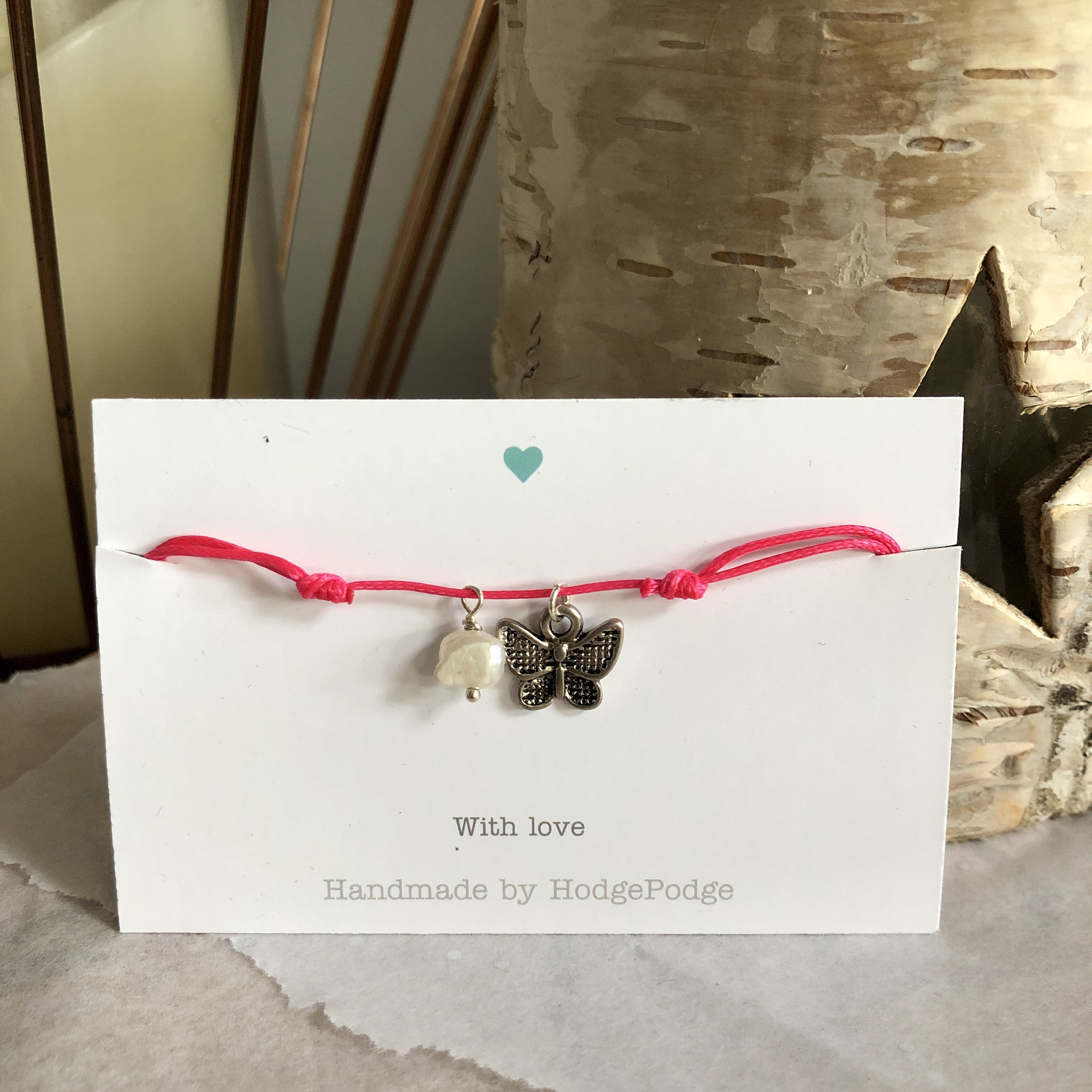 Adjustable cord bracelet with butterfly charm and pearl