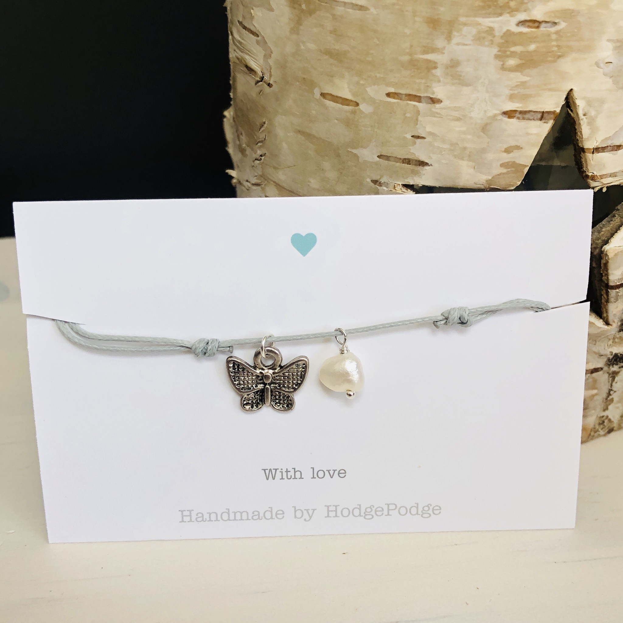 Adjustable cord bracelet light grey with small butterfly