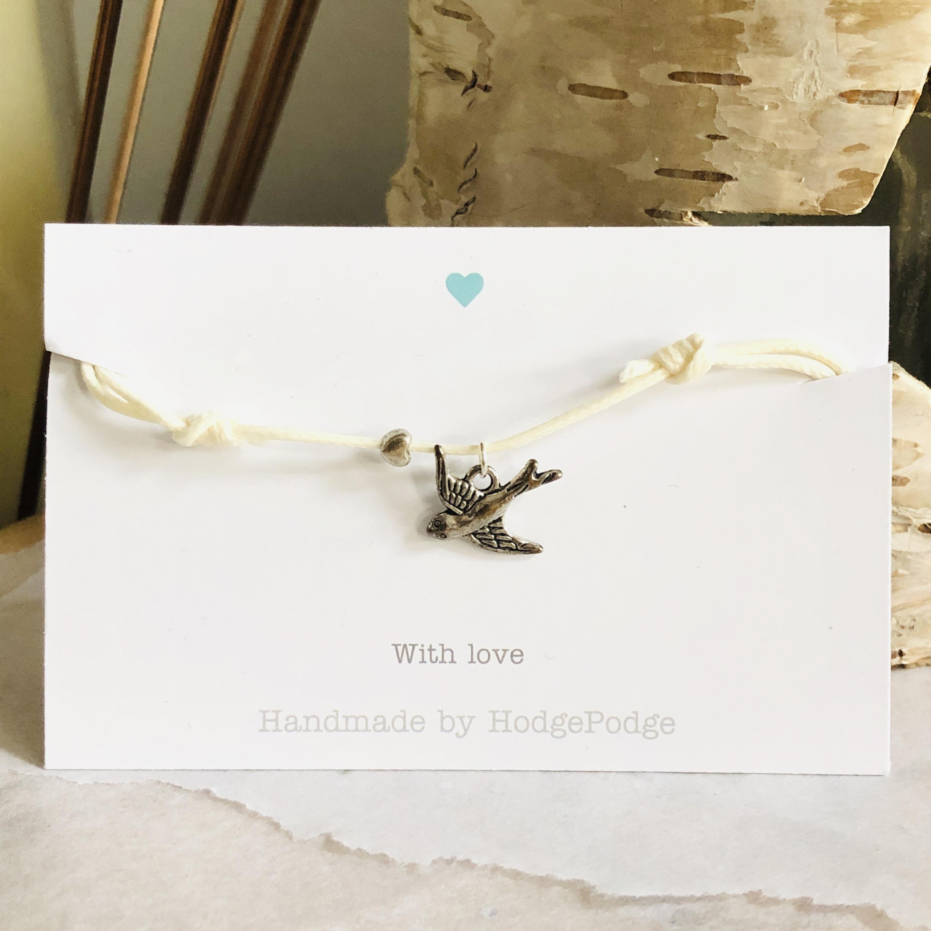 Adjustable cord bracelet with bird charm (cream)