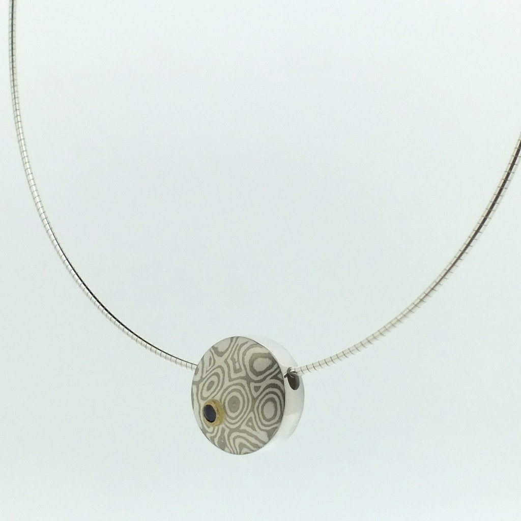 18k white gold and silver mokume gane small discus pendant with blue sapphire in a 22k gold setting