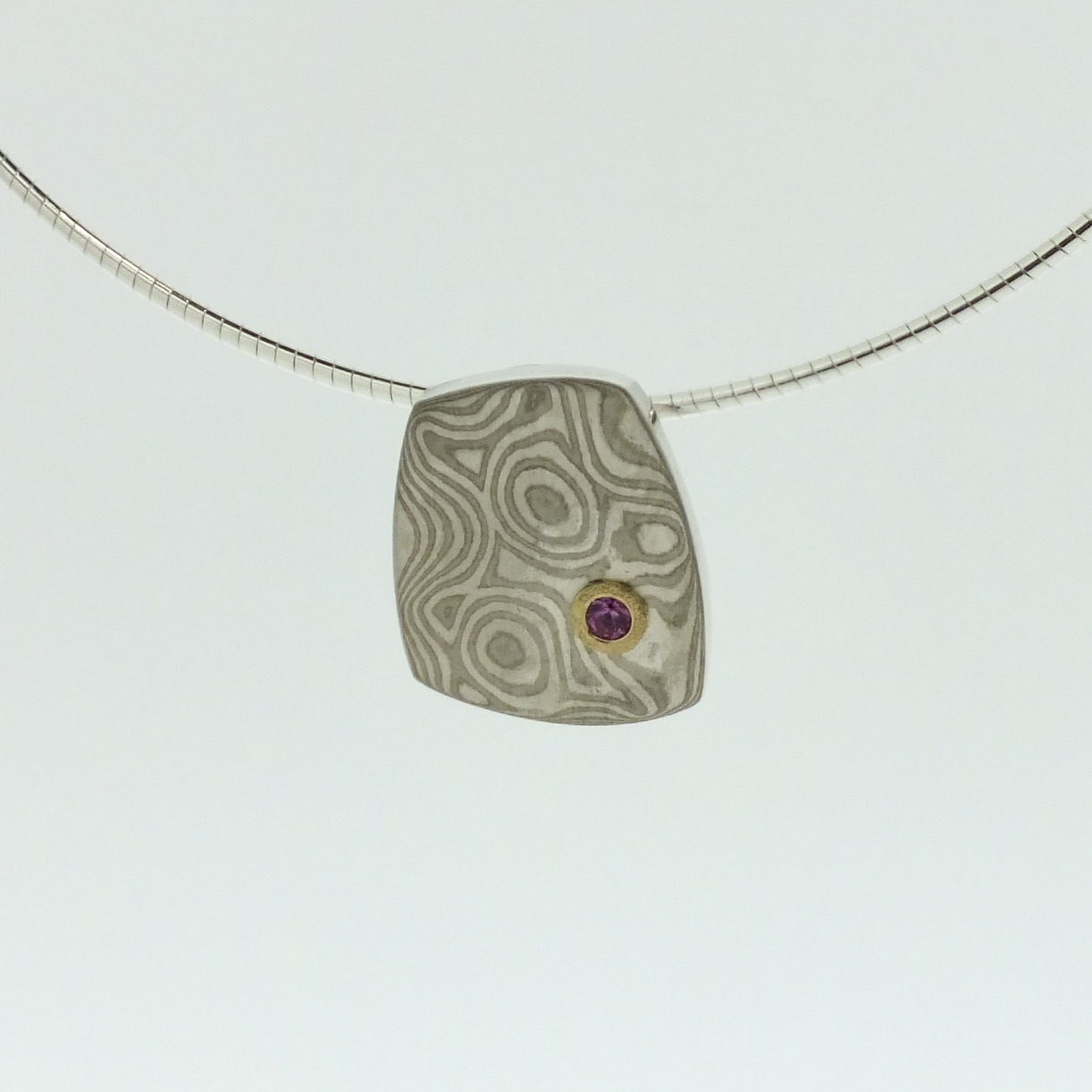 18k white gold and silver mokume gane small Fower Neukit pendant with pink sapphire in 22k gold setting