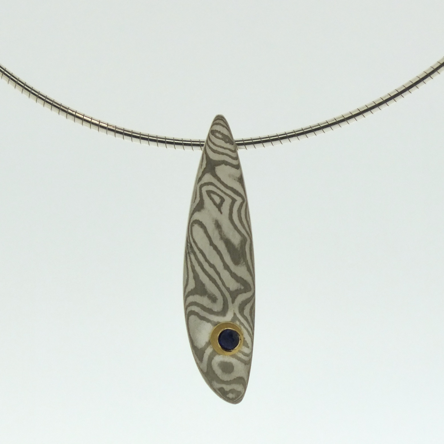 18k white gold and silver mokume gane small Sgiath pendant with blue sapphire in 22k gold setting