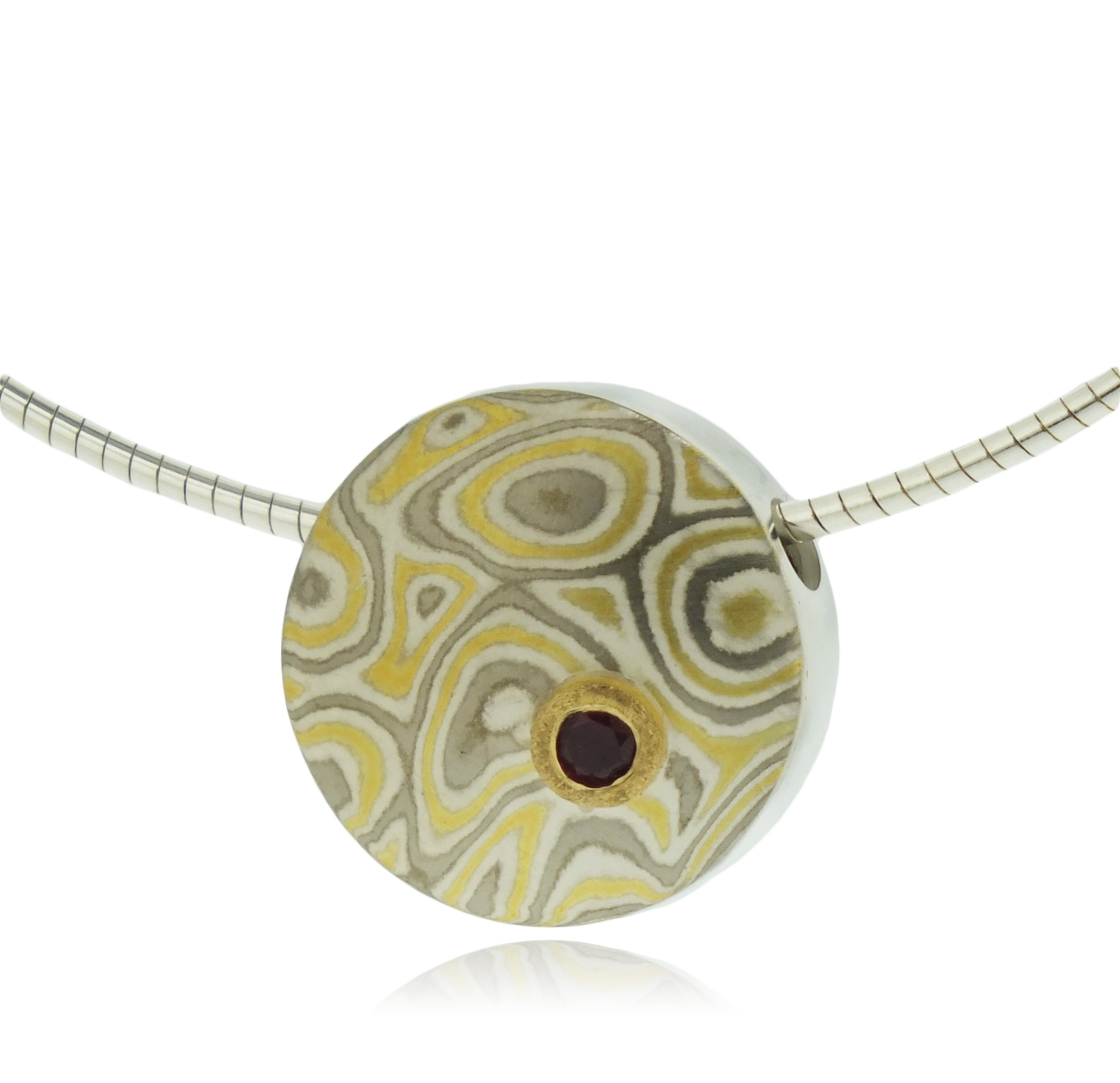 Mokume gane small discus pendant in  22k gold, 18k white gold and silver with ruby set in 22k gold