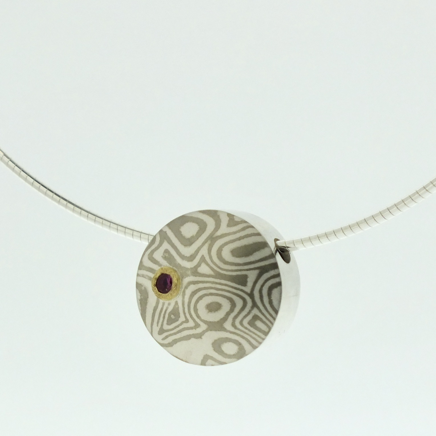 18k white gold and silver mokume gane pendant with pink sapphire in 22k gold setting