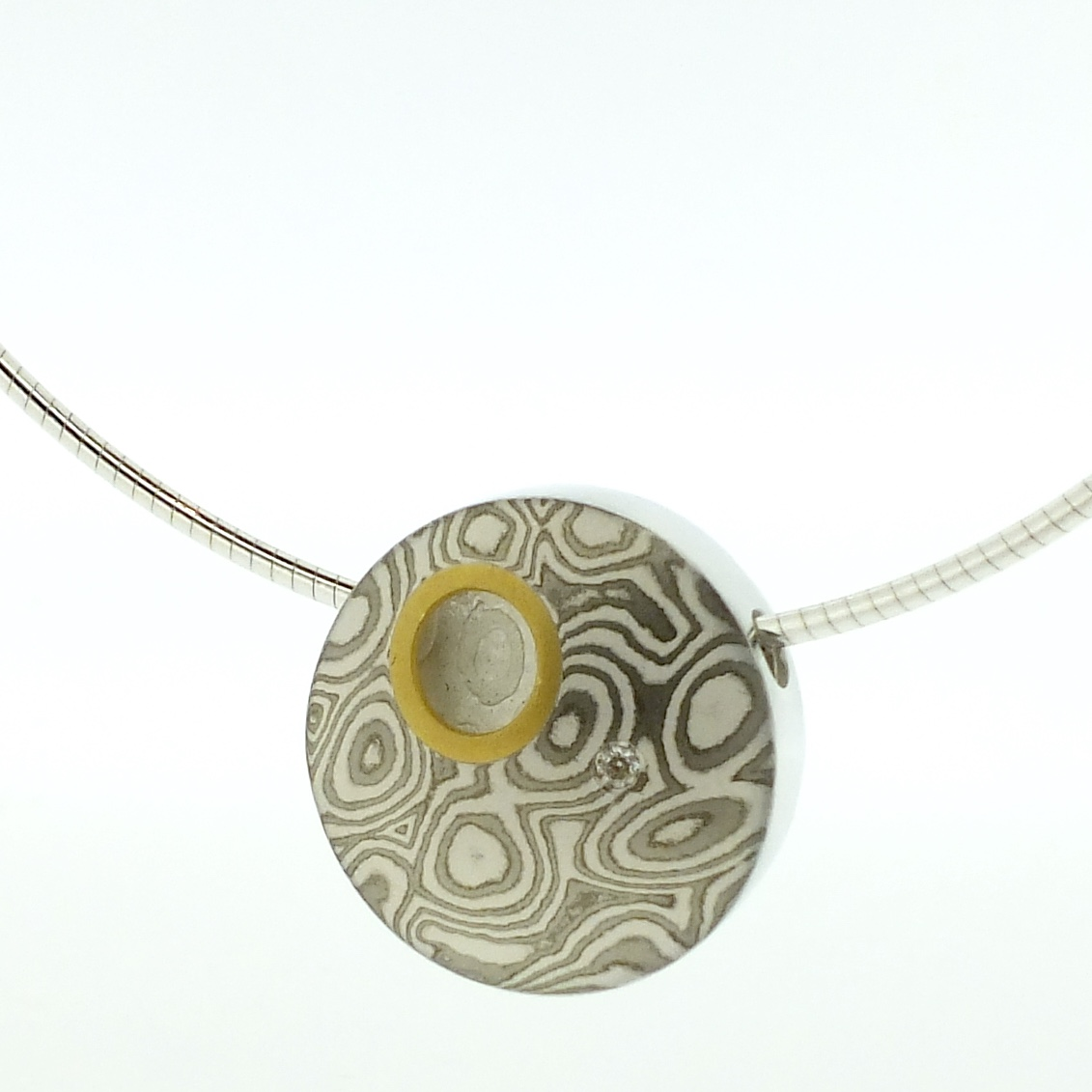 18k white gold and silver mokume gane medium discus pendant with 22k gold rimmed cutaway and diamond detail