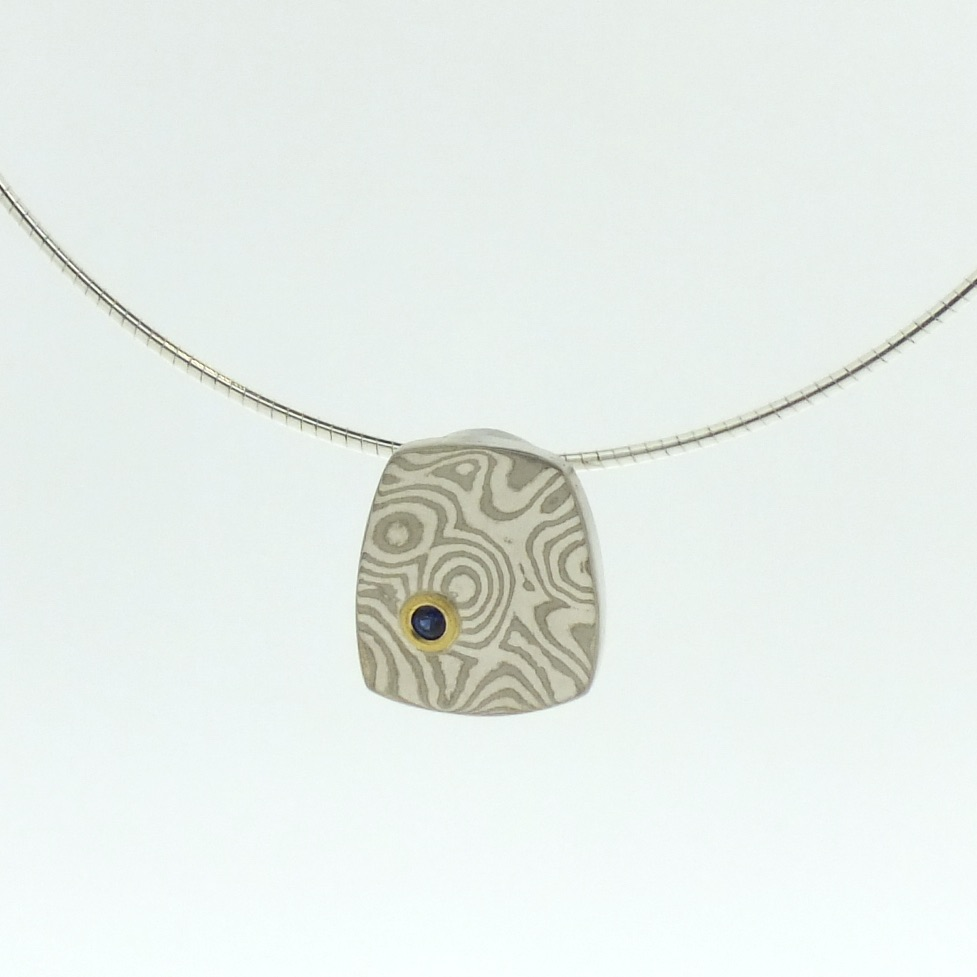 18k white gold and silver mokume gane small Fower Neukit pendant with blue sapphire in 22k gold setting
