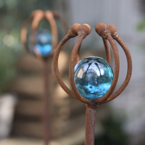 Rostig dekorativ pinne med blå kula